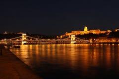 布达城堡和铁锁式桥梁在晚上 图库摄影