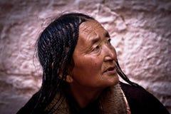 布达拉宫拉萨西藏的一个老妇人 免版税库存照片