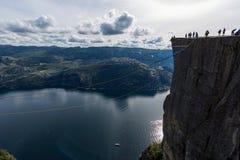 布道台,挪威- 2015年8月31日:坐在布道台边缘的游人 一多数populat地方在挪威 图库摄影