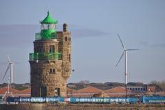 布里曼、德国- 2017年11月6日, -在海港入口的灯塔与工业存贮藏库和风力驻地 免版税库存图片