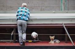 布里曼,德国- 2018年6月19日, -倾斜在与他的扶手栏杆的方格的衬衣的老人往与被点燃的他的照相机 库存照片
