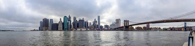 布鲁克林大桥和曼哈顿的全景照片有到达云彩在纽约,团结的状态的摩天大楼的上面的 免版税库存照片