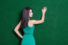 布鲁内特夫人对从后面的绿色墙壁 库存图片