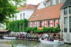布鲁日,比利时- 2010年8月:站立在码头的一个队列的游人他们的沿城市的运河的小船旅行的 图库摄影