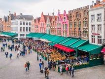 布鲁日,比利时- 2015年10月18日:集市广场在有五颜六色的房子和咖啡的布鲁日从事园艺, 10月的比利时 免版税库存照片