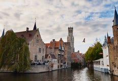 布鲁日,西弗拉芒省,比利时,2018年10月19日:中世纪大厦、塔钟楼和从Rozenhoedkaai的水运河看法  库存照片