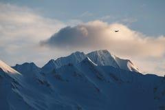 布什飞机飞行在遥远的阿拉斯加山脉在日落 免版税库存照片