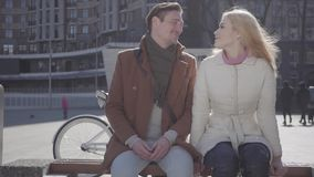 帅哥和俏丽的白肤金发的妇女坐在城市街道的温暖的夹克的有后边自行车,谈话和微笑的 影视素材
