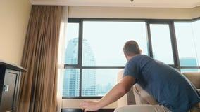 帅哥在有俯视摩天大楼的一个全景窗口的一间屋子里包装一个手提箱 股票视频