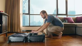 帅哥在有俯视摩天大楼的一个全景窗口的一间屋子里包装一个手提箱 影视素材