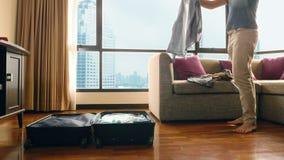 帅哥在有俯视摩天大楼的一个全景窗口的一间屋子里包装一个手提箱 股票录像
