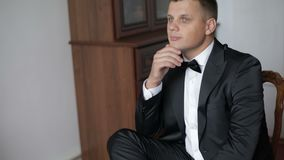 帅哥坐在黑衣服的一把椅子与蝶形领结 商人 慢的行动 股票视频