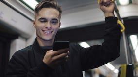 帅哥画象拿着在公共交通工具的扶手栏杆浏览智能手机 他读书喜讯 股票录像