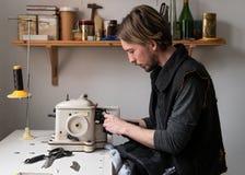 帅哥裁缝在车间缝合在更加毛茸的机器的毛皮 免版税库存照片