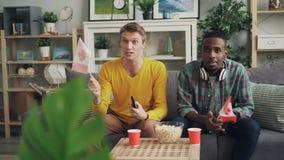帅哥观看在电视的竞争拿着加拿大旗子然后庆祝胜利的体育迷获得乐趣 影视素材