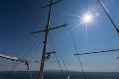 帆柱和索具在蓝天与太阳 免版税图库摄影
