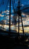 帆柱和绳索在天空日落背景的风船船 免版税库存照片