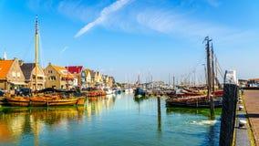 帆船和汽船在海藻追上的港口的部分停泊了在Urk历史的渔村  库存图片