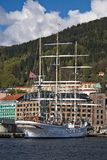 帆船在城市 在船的挪威旗子 与云彩的蓝天,与forrest的小山 免版税库存图片