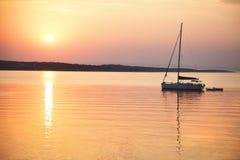 帆船在风平浪静漂浮在日出 库存图片