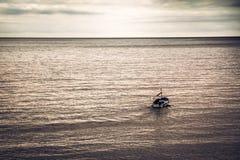 帆船风帆到往天际的海里在与拷贝空间的日落期间在象征起点的紫色被定调子的颜色 图库摄影