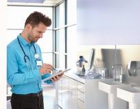医师与片剂一起使用在医生办公室 库存图片