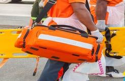 医师准备箱子袋子急救工具和黄色担架医疗设备 免版税库存图片