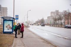 希奥利艾,立陶宛- 2018年4月04日:等待在公共汽车站,希奥利艾,立陶宛的人们 城市是著名的太阳在downtow的男孩雕象 库存照片