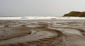 希望与风大浪急的海面的小海湾海滩在一多云天 免版税库存图片
