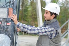 希望入建筑机器的建筑工人 免版税库存照片