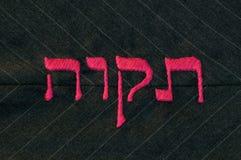 希望在希伯来语语言,缝在织品 库存照片