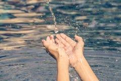 希望概念:人的手用水倒下到棕榈 免版税库存图片