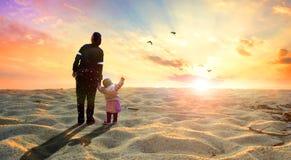 希望的概念:母亲和孩子在沙漠 库存照片