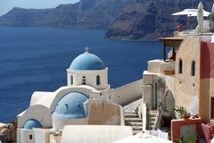 希腊传统正统基督教会在圣托里尼海岛边缘火山破火山口的Oia村庄  免版税库存照片