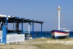 希腊小酒馆有海视图和小船 免版税库存照片