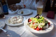 希腊沙拉和tzatziki的板材在桌上,户内 库存图片