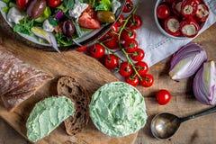 希腊沙拉用西红柿、葱、开胃小菜、匙子和moretum罗马pesto在木台式视图 免版税库存照片