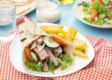 希腊电罗经用猪肉、菜和自创皮塔饼面包 图库摄影