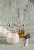 希腊酸奶和蜂蜜在一个玻璃瓶子蓝色木表面上 免版税库存图片