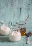 希腊酸奶和蜂蜜在一个玻璃瓶子蓝色木表面上 图库摄影