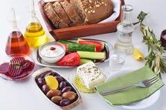 希腊食物, mezedes 有橄榄油和藤醋的,橄榄,希脂乳, tzatziki,黑面包, raki,甜菜根瓶子,新鲜 库存图片