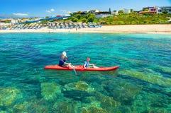 希腊,克利特海岛, 7月, 07,2011 :红色小船独木舟的两个男孩兄弟在爱琴海青绿的水中划皮船 Aldemar旅馆s 库存图片