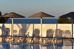 希腊,圣托里尼,由游泳场的太阳床 免版税库存图片
