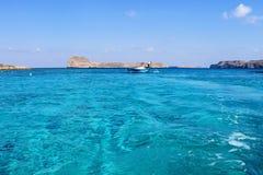 希腊 在夏天,在海岛附近的两条小船在蓝色盐水湖 库存图片