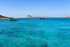 希腊 在夏天,在海岛附近的两条小船在蓝色盐水湖 库存照片