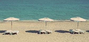 希腊 海滩睡椅希腊海岛kefalos kos桔子伞 椅子和伞在Kefalos海滩 我 免版税库存图片