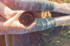 帐篷和拿着的一个杯子女孩远足者温暖的茶 山和湖在背景中 免版税库存图片