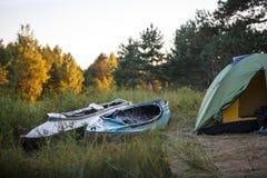 帐篷在根据太阳,黄色和绿色帐篷的森林里 图库摄影