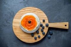 帕夫洛娃与奶油、杏子和有些蓝莓的蛋白甜饼蛋糕 免版税库存照片