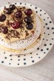 帕夫洛娃蛋糕用在陶瓷板材垂直的新鲜的樱桃 免版税库存图片